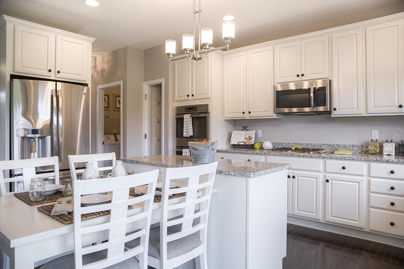 White kitchen with island and dining table in New home in Dutchess County's Sleight Farm at LaGrange, located in the Hudson Valley